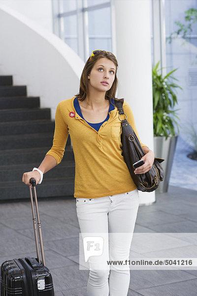 Frau mit Handy und Trolley-Tasche
