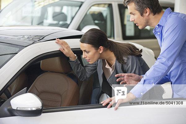 Paar  das ein Auto vor dem Kauf untersucht.