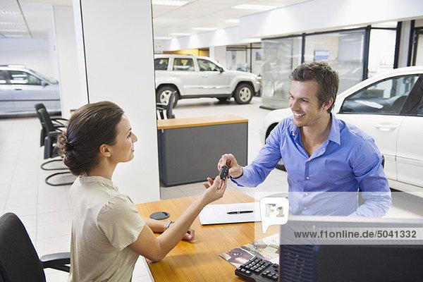 Verkäuferin mit Autoschlüssel zu einem Mann