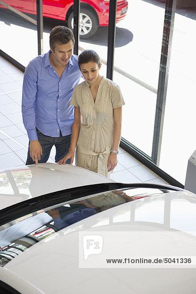 Ein Paar schaut sich ein Auto in einem Ausstellungsraum an.