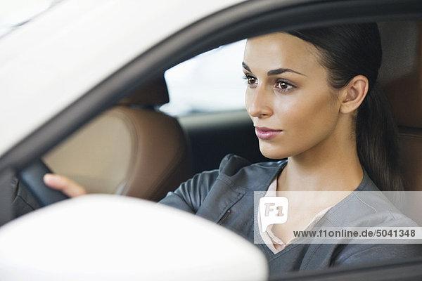 Schöne junge Frau bei einer Probefahrt