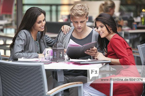 Junger Mann mit zwei jungen Frauen auf der Speisekarte eines Restaurants