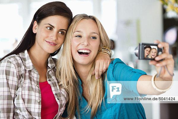 Weibliche Freunde  die mit einer Kamera ein Foto von sich machen