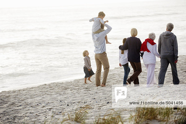 Multi-generation family walking on the beach