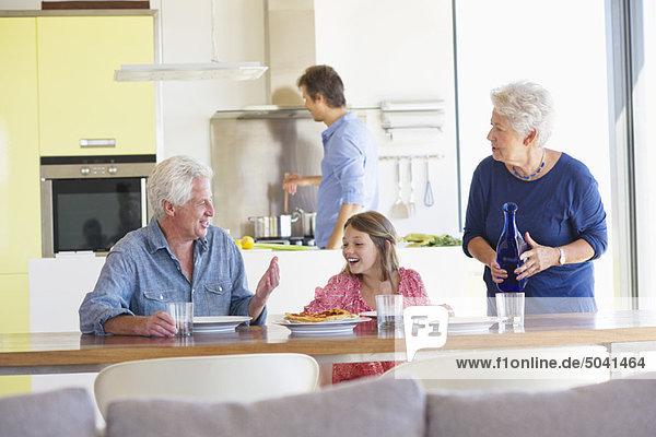 Mädchen sitzt mit ihren Eltern am Esstisch und ihr Vater kocht im Hintergrund.