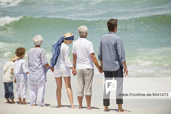 Mehrgenerationen-Familie in einer Reihe am Strand stehend