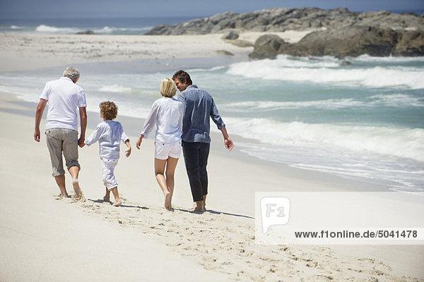 Rückansicht einer Mehrgenerationen-Familie beim Spaziergang am Strand