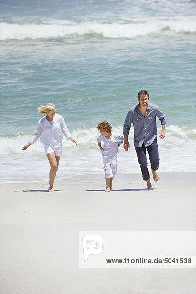Paar mit ihrem Sohn  der am Strand rennt.