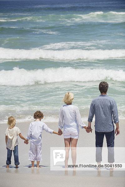 Paar mit zwei Kindern am Strand stehend