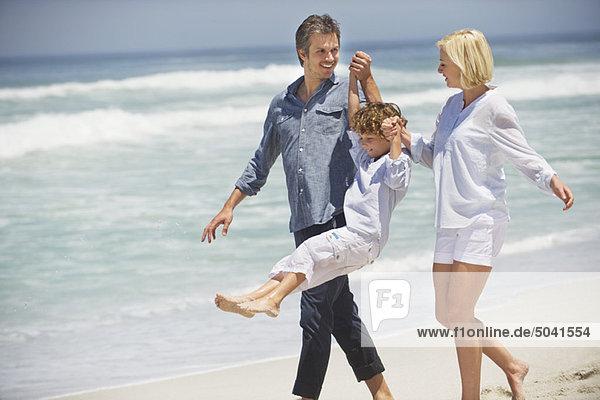 Ein Paar  das mit seinem Sohn am Strand spazieren geht.