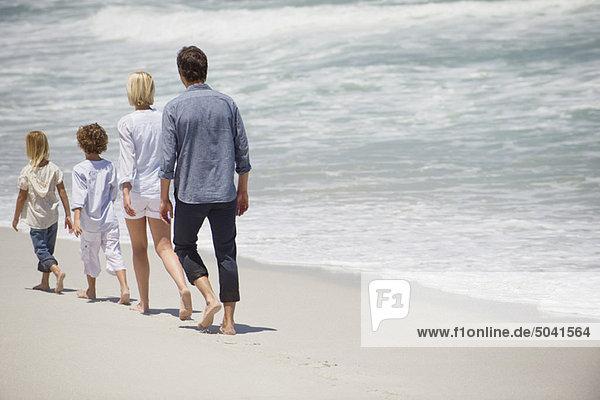 Paar mit zwei Kindern  die am Strand spazieren gehen