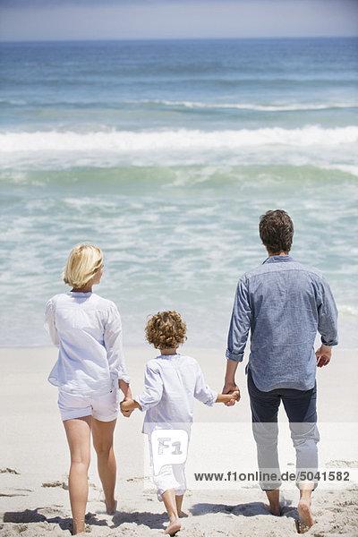 Paar mit ihrem Sohn  der am Strand spazieren geht.