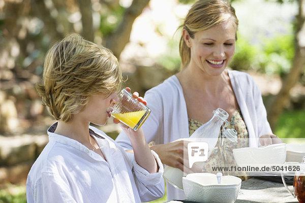 Mutter beim Essen mit ihrem Sohn im Freien