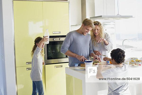 Paar mit ihren beiden Kindern beim Zubereiten von Essen in einer häuslichen Küche