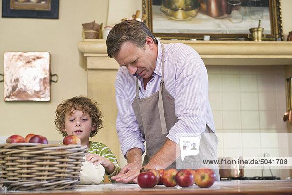 Süßer kleiner Junge und sein Vater kneten Teig in der Küche.
