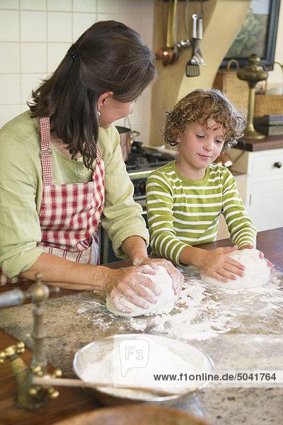 Großmutter und kleiner Junge beim Teigkneten in der Küche