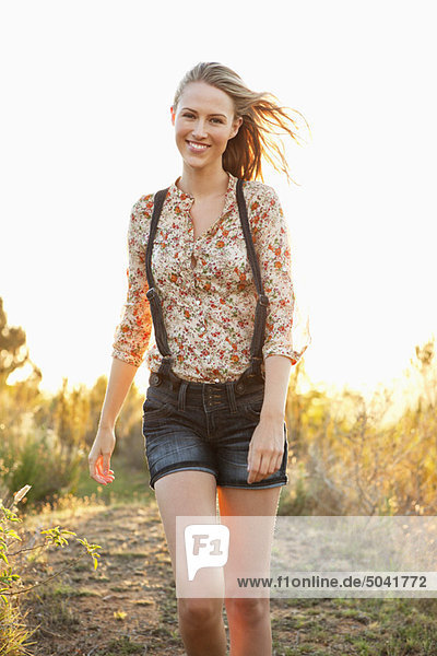 Beautiful woman walking on a trail and smiling