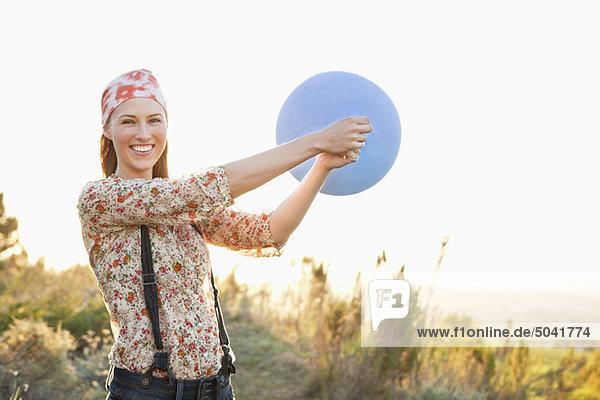 Schöne Frau spielt mit einem Ballon und lächelt.