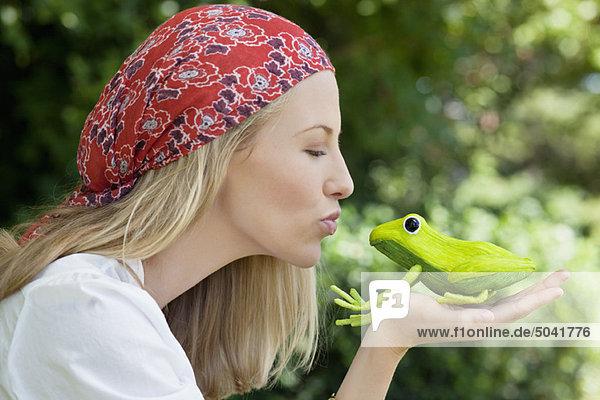 Junge Frau küsst Froschspielzeug