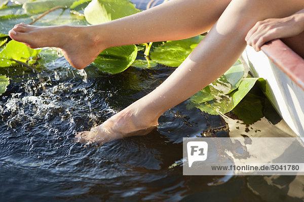 Frau liegt in einem Boot und taucht ihre Beine in einen Teich.