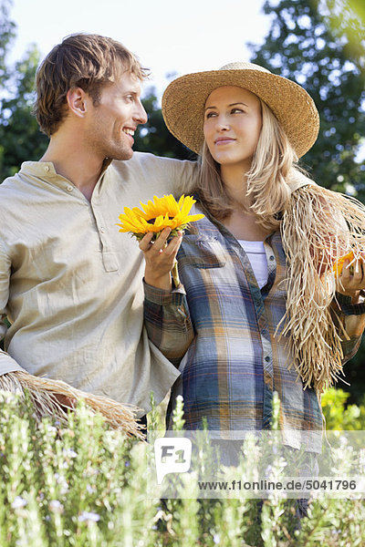 Junges Paar in Vogelscheuchenpose auf einem Feld