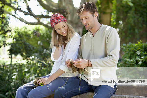 Young couple knitting together and smiling
