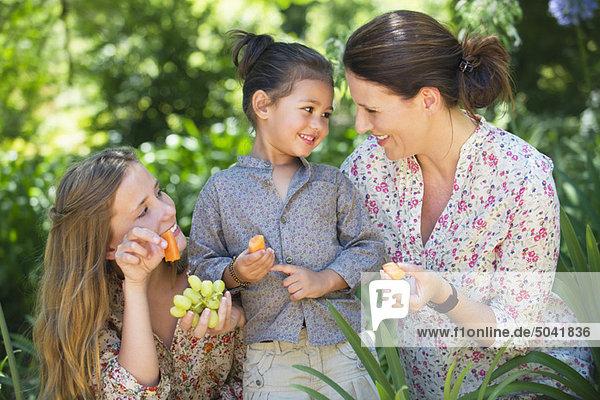 Glückliche Mutter isst Früchte mit ihren beiden Töchtern im Freien.