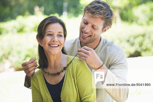 Mann  der Moms Halskette im Freien befestigt.
