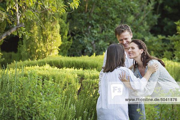Ein reifes Paar  das seine Mutter im Garten umarmt.