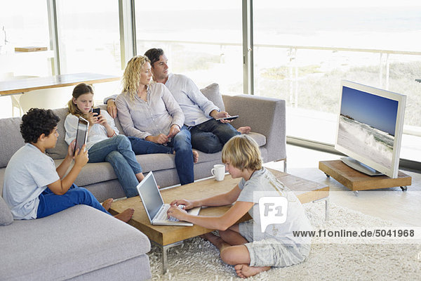 Paare  die fernsehen  während ihre Kinder in verschiedenen Aktivitäten beschäftigt sind