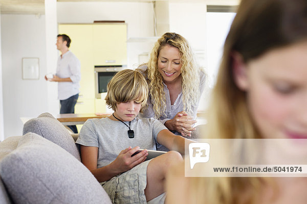 Teenager-Junge  der ein digitales Tablett benutzt  während seine Mutter ihn ansieht und lächelt.