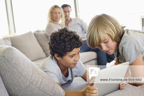 Brüder  die ein digitales Tablett benutzen  während ihre Eltern sie anschauen.