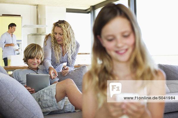 Teenager-Junge mit einem digitalen Tablett  seine Mutter steht hinter ihm und lächelt.