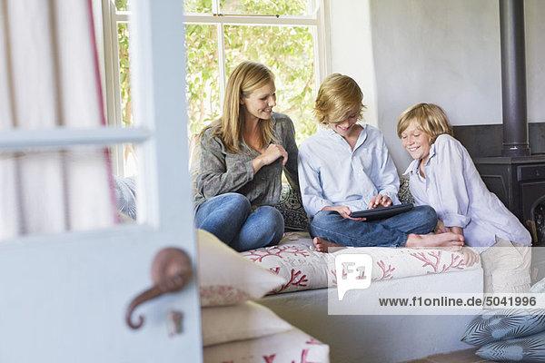 Kinder und ihre Mutter mit digitalem Tablett im Haus