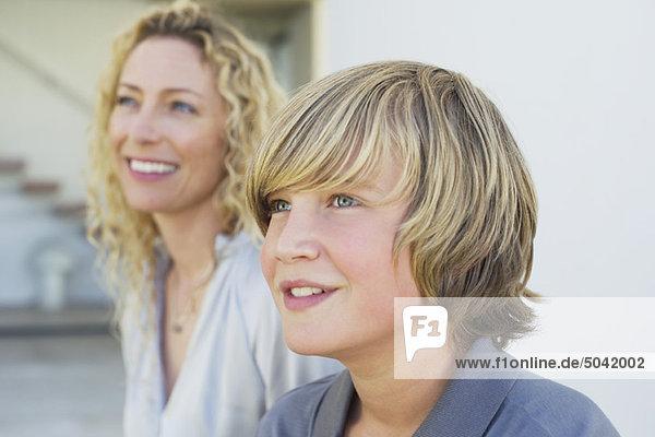 Nahaufnahme eines Teenagers  der mit seiner Mutter lächelt.
