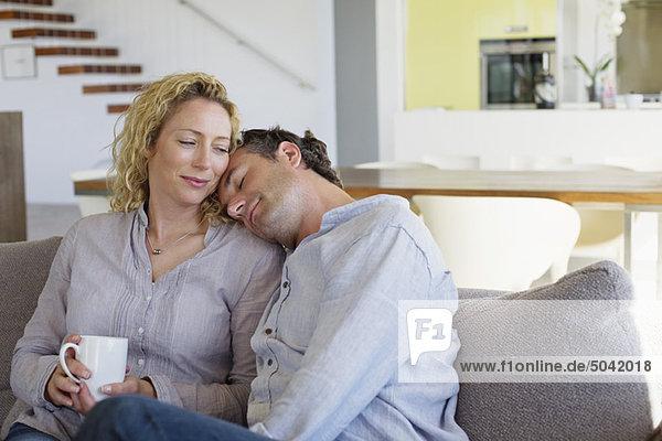 Mann legt seinen Kopf auf die Schultern einer Frau.