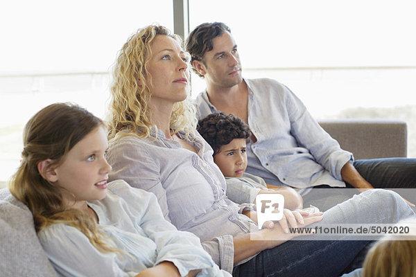 Familie mit drei Kindern auf einer Couch sitzend