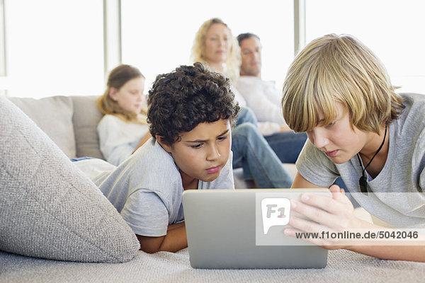 Teenager-Junge mit einem digitalen Tablett mit seinem Bruder und seiner Familie im Hintergrund