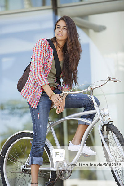 Junge Frau sitzt auf dem Fahrrad und schaut weg.