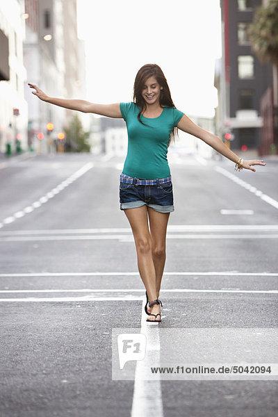 Junge Frau  die auf Straßenmarkierung geht und sich selbst ausbalanciert.