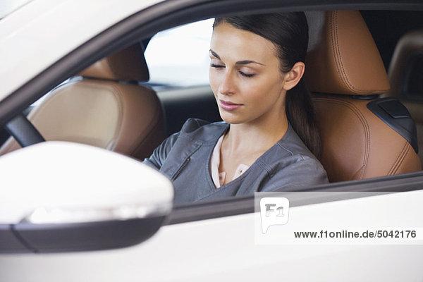 Schöne junge Frau sitzt mit geschlossenen Augen im Auto.