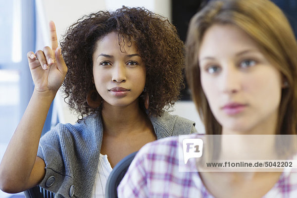 Two women sitting in classroom with focus on African American woman raising hand