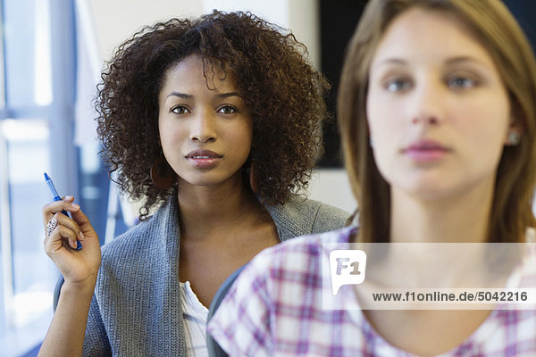 Two women sitting in classroom with focus on African American woman