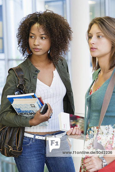 Two women looking away while holding books