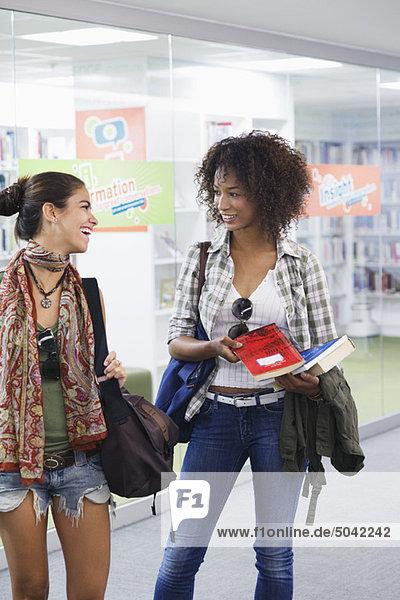 Universitätsstudenten  die sich in einer Bibliothek gegenseitig suchen