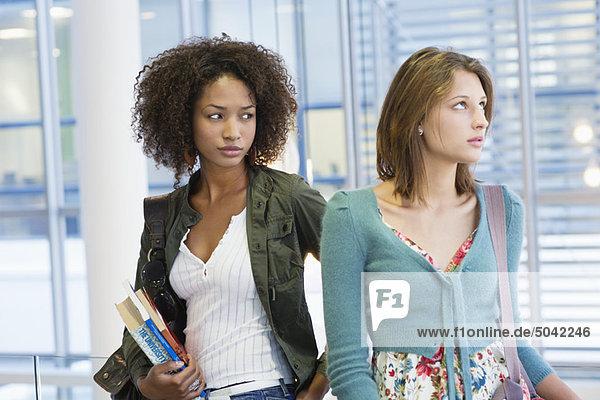 Zwei Frauen  die mit Büchern in der Hand an der Universität weggucken.