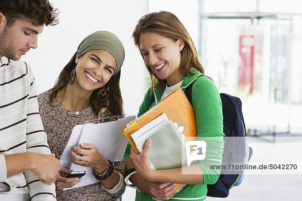 Drei Studenten stehen zusammen und lächeln