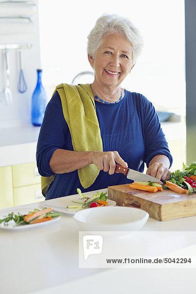 Porträt einer älteren Frau  die in einer Küche Gemüse schneidet.