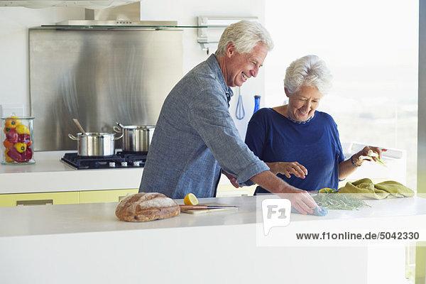 Seniorenpaar beim Putzen der Küchenzeile