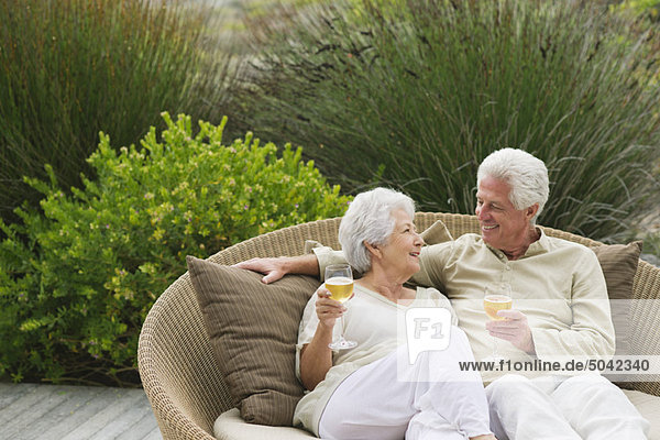 Senior couple sitting in a wicker couch and smiling